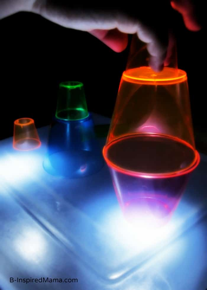 Stacking Colorful Cups on a Kids Light Box at B-Inspired Mama