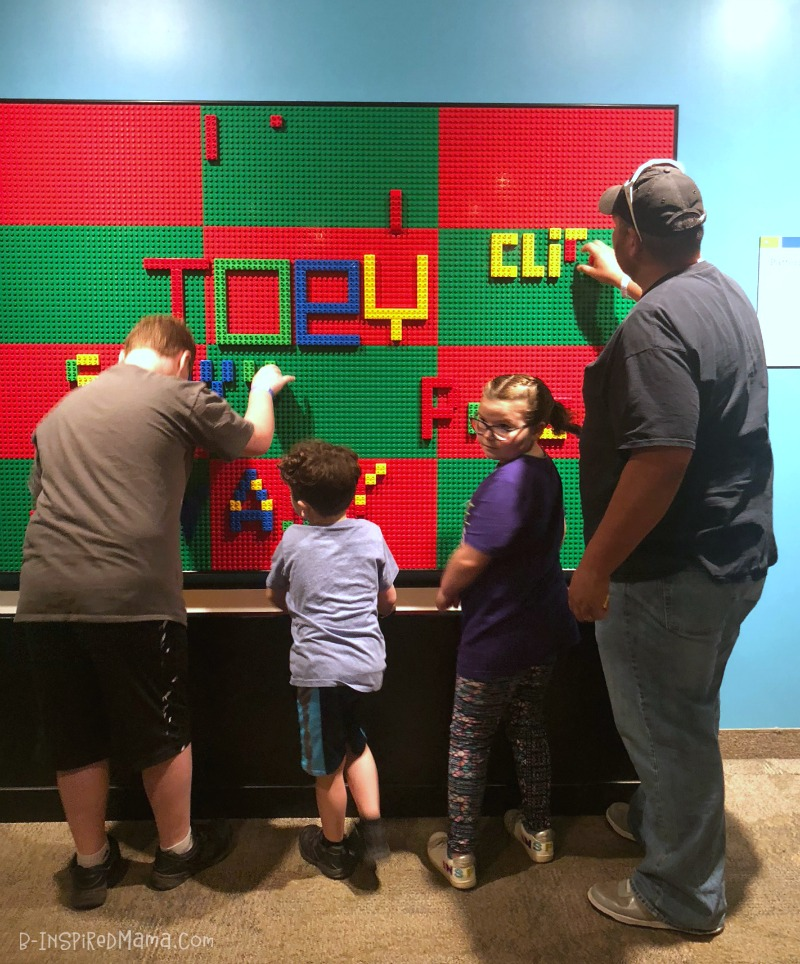 Cliff and the kids spelling their names on the LEGO wall - at The Strong museum